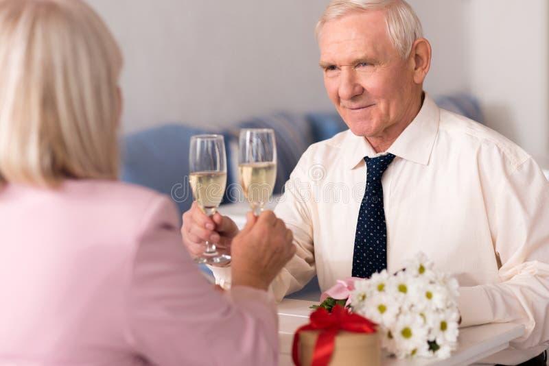 敬酒他的夫人秀丽的殷勤老人 免版税库存照片