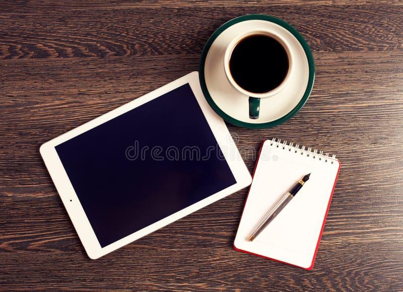 数字式有便条纸和咖啡的片剂计算机在老木书桌上的 库存图片