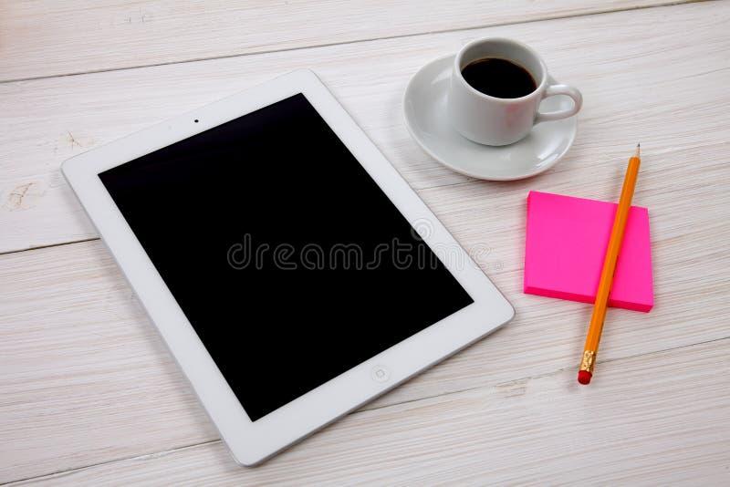 数字式片剂、笔记薄和咖啡在木背景的 免版税库存照片
