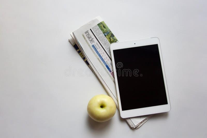 数字式片剂、被折叠的报纸和苹果 图库摄影