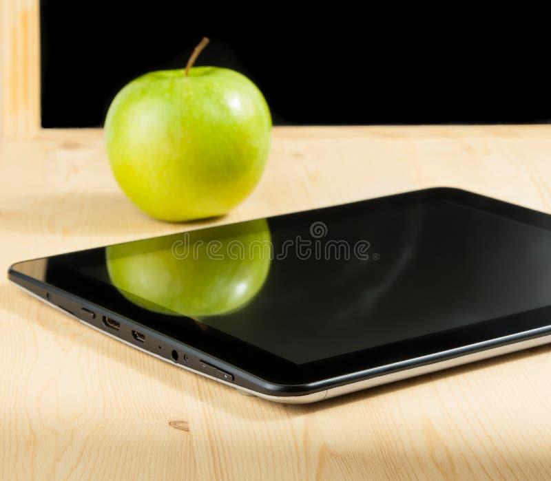 数字式片剂个人计算机和绿色苹果在黑板前面在木桌上 免版税库存照片
