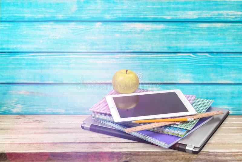 数字式片剂和书在桌上 免版税库存照片