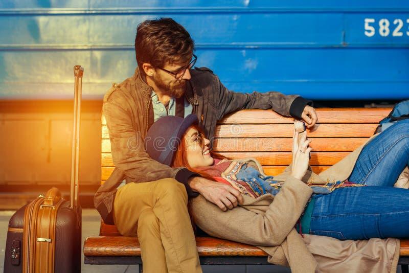 数字技术和旅行 在行家的年轻爱恋的夫妇佩带使用片剂计算机,当坐在火车站wai时 免版税库存图片