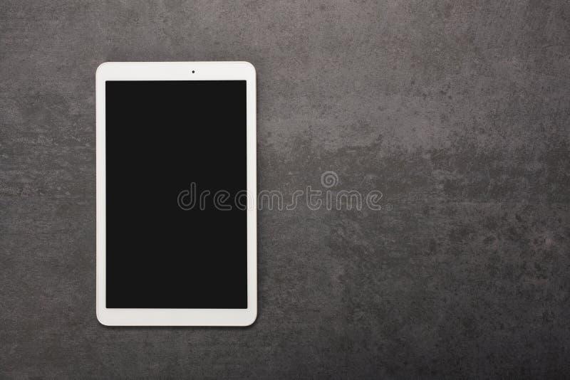 数字片剂屏幕有在灰色石背景的裁减路线与拷贝空间 免版税库存图片