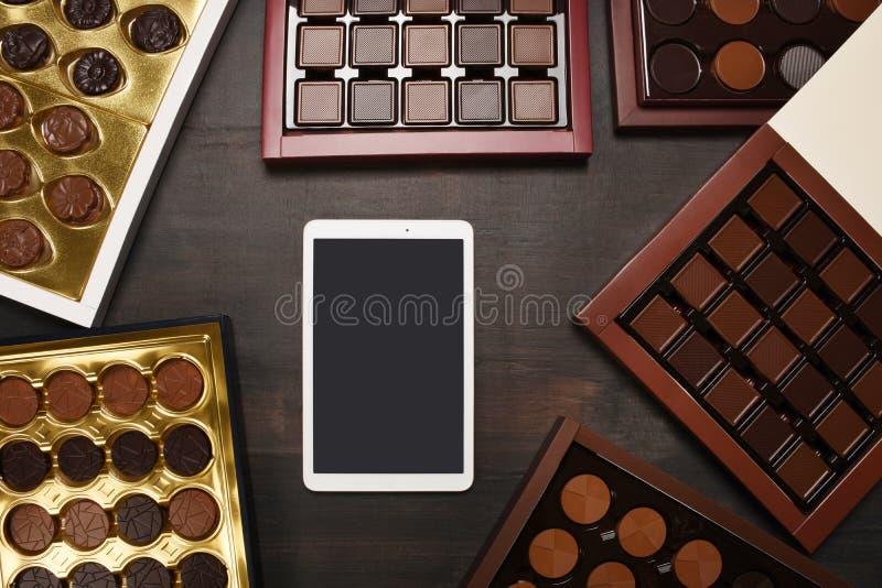 数字片剂屏幕有有小组的裁减路线在木纹理的巧克力箱子 免版税库存图片