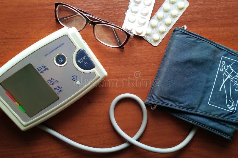 数字血压显示器、玻璃和药片在棕色桌上 库存照片