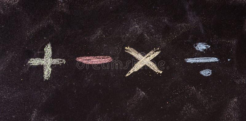 数学符号写与五颜六色的白垩,在黑板背景 图库摄影