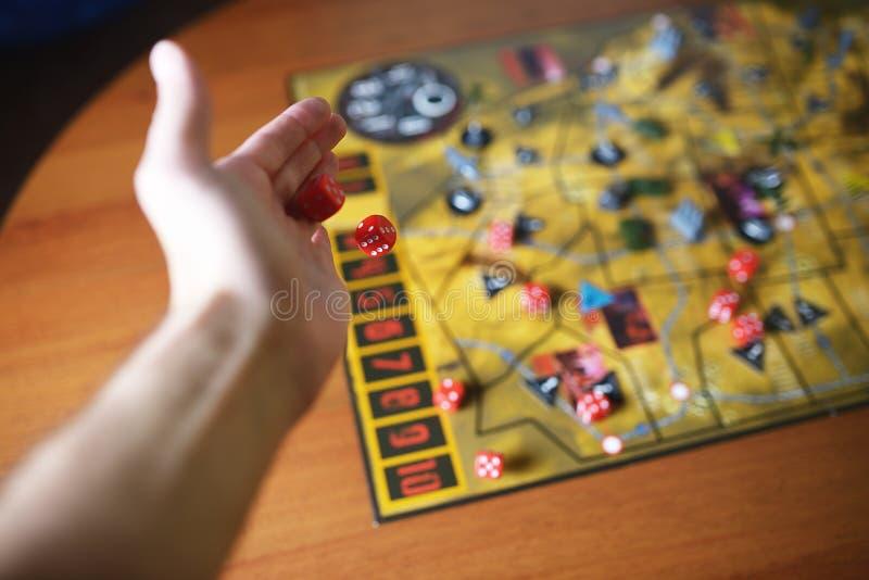 数滚动的红色模子在与boardgame的一张桌上落 Gameplay片刻 免版税库存照片