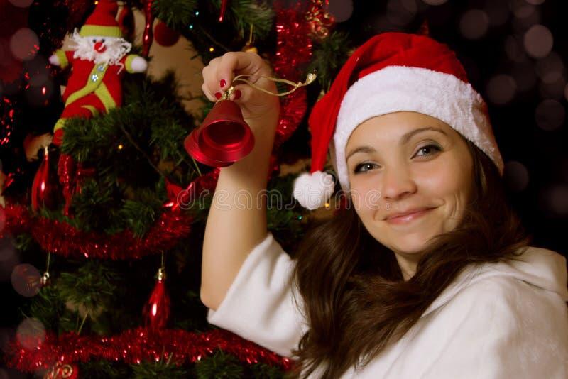 敲响响铃的妇女在圣诞树下 免版税库存照片