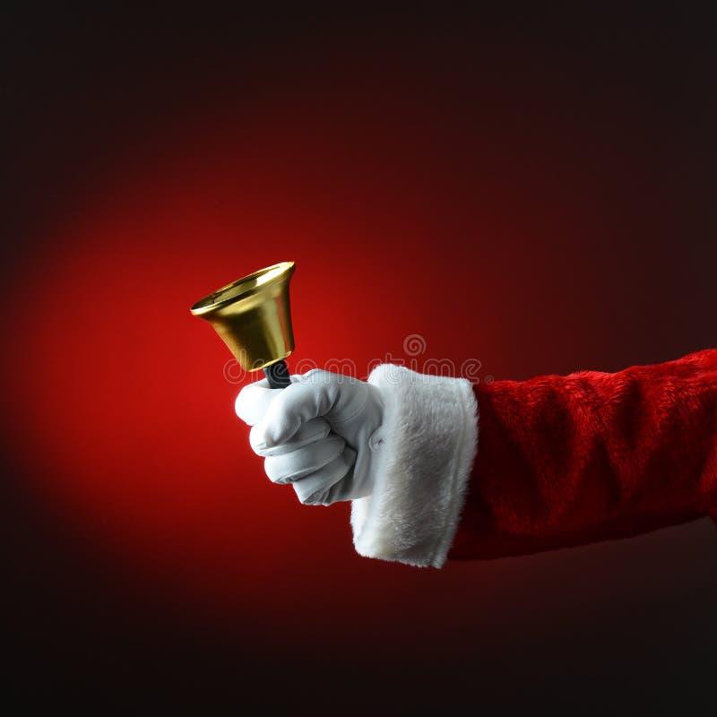 敲响在光的圣诞老人响铃对深红背景 库存照片