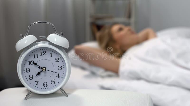 敲响在床头柜愉快的夫人醒,健康生活方式的白色闹钟 图库摄影