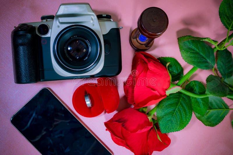 敲响在红色箱子、美丽的红色玫瑰、电话、照相机和滴漏 库存照片
