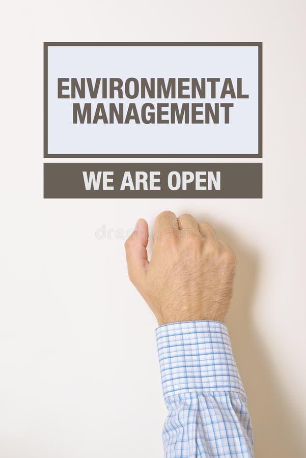 敲环境管理办公室门的商人 免版税库存图片