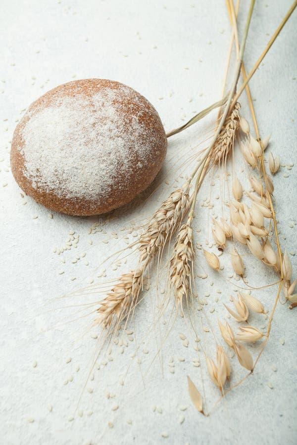 整个五谷黑麦和燕麦的黑面包和耳朵在白色背景 库存照片
