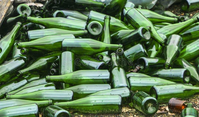 整个和残破的绿色瓶,在路面的谎言山 概念:垃圾回收废物,处置和玻璃对象 库存图片