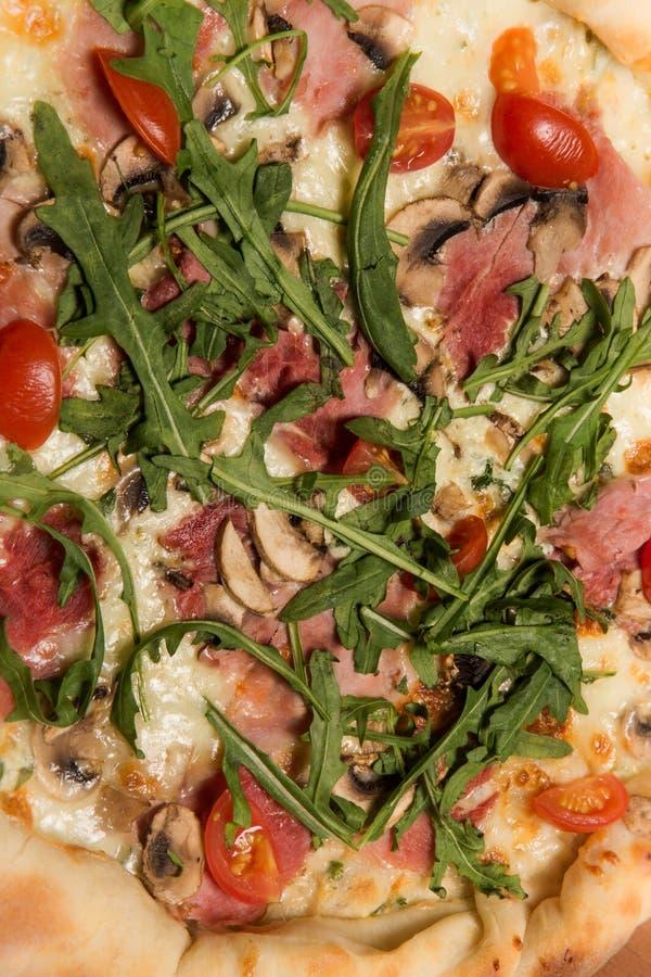 整个比萨顶视图宏指令与芝麻菜、火腿和蕃茄的 免版税库存照片