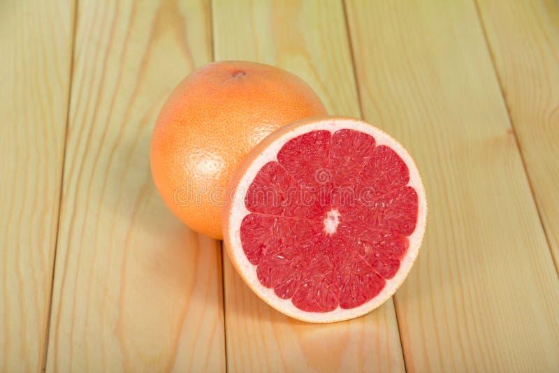 整个葡萄柚和被切的切片在桌上 库存图片