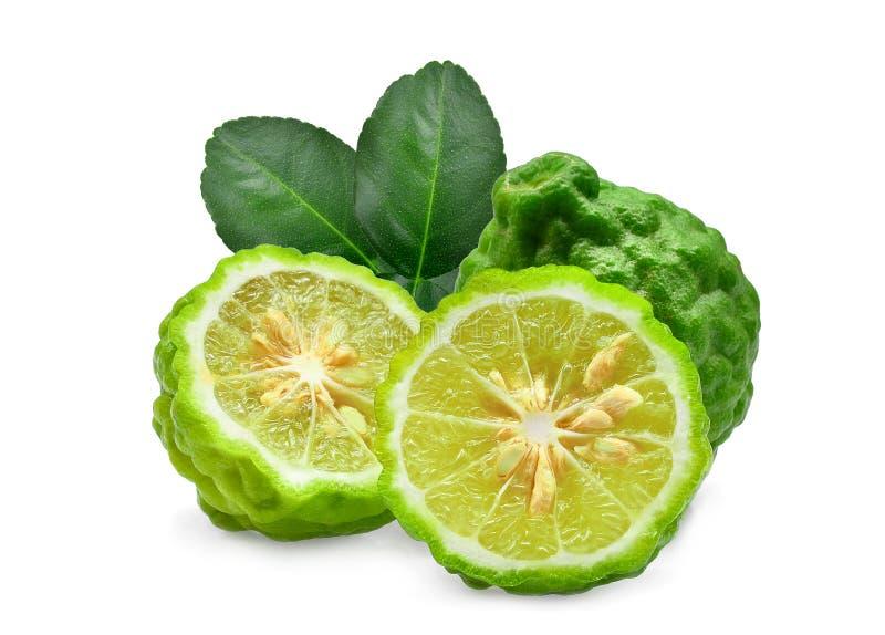 整体和半新鲜的香柠檬与被隔绝的绿色叶子 免版税图库摄影