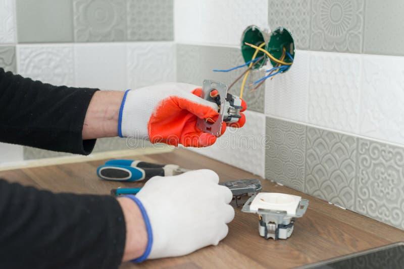 整修和建筑在厨房,电工特写镜头递安装出口在有瓷砖使用的墙壁 免版税库存图片