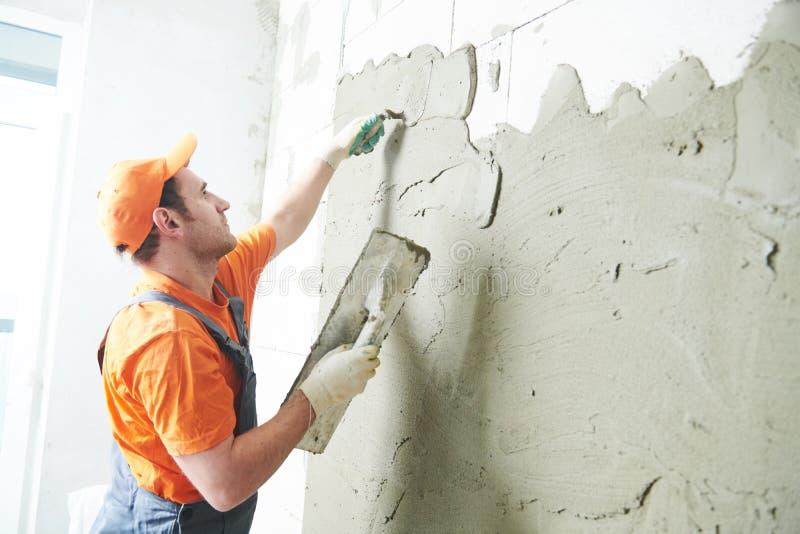 整修在家 在墙壁上的石膏工传播的膏药 免版税库存照片