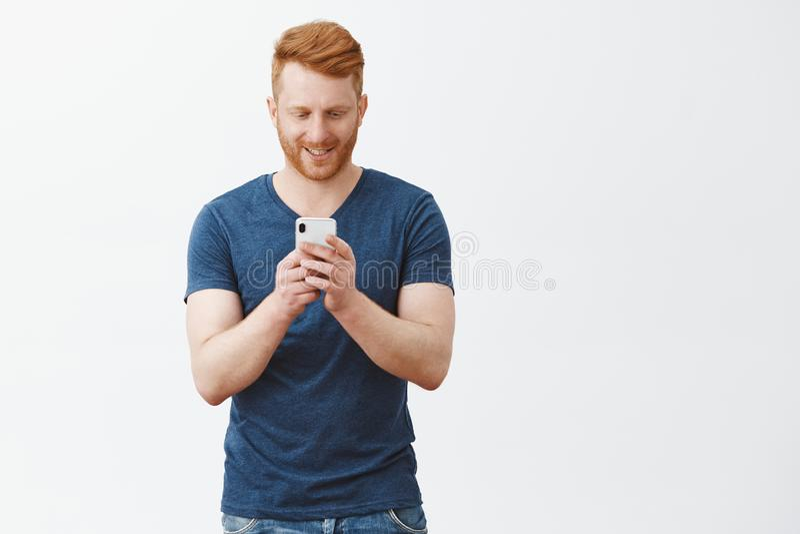 整天打在智能手机比赛的人,不可能被激发和兴奋的休假 英俊的感情红头发人男性 库存图片