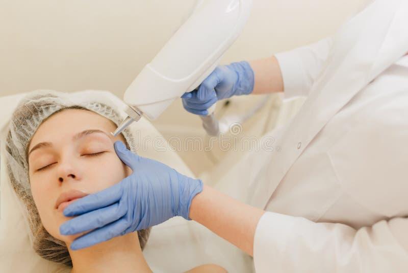 整容术做法,俏丽的年轻女人的回复发廊的 皮肤学做法,在蓝色的手发光 免版税库存照片