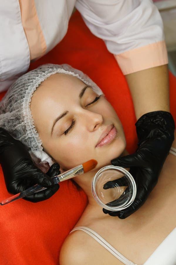整容术 美容师应用在客户的面孔的润湿的面具 防皱治疗 库存图片