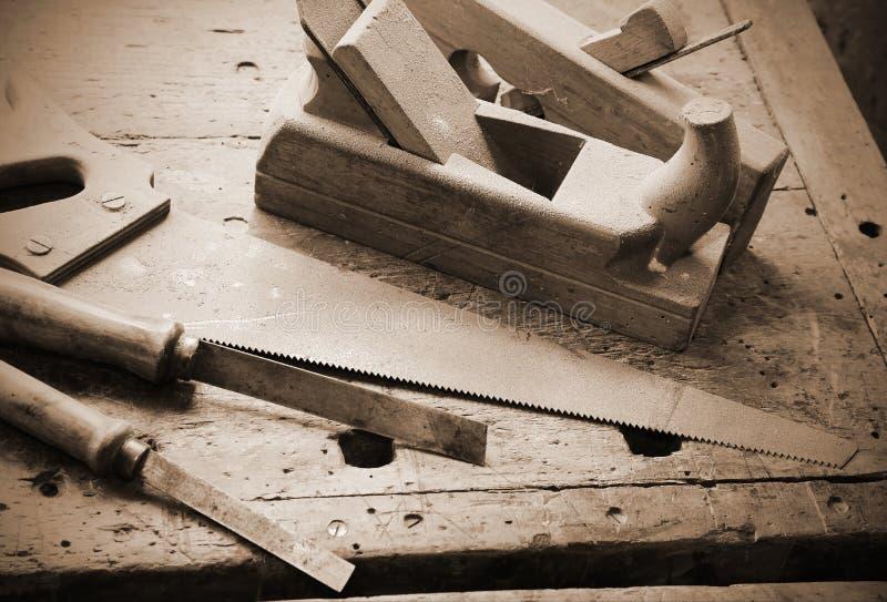 整平机和凿子和手在有老的工作凳看见了 库存照片