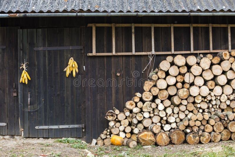 整洁地堆积了在冬天准备的大堆切好的火木日志在有石板屋顶、梯子和玉米的葡萄酒木谷仓墙壁 图库摄影