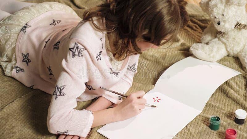 整洁地画与在她的册页,爱好的树胶水彩画颜料美丽的花的有天才的女孩 免版税库存照片