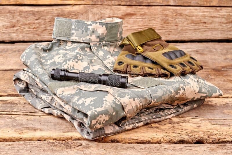 整洁地被折叠的军事伪装穿衣与手套和火炬 图库摄影