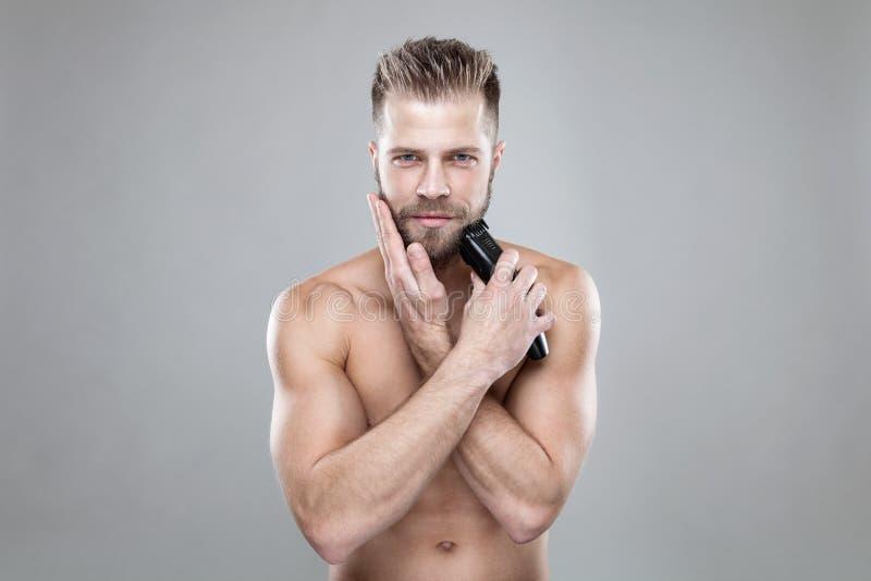 整理他的与整理者的英俊的有胡子的人胡子 免版税库存图片