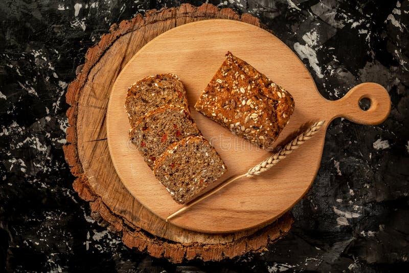 整粒面包和切片大面包在木切板 r 与种子的整个五谷黑麦面包 能转化为酮的低气化器 库存照片