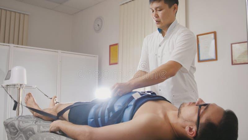 整骨疗法医生执行做法,舒展脊椎,按摩脊柱治疗者,亚洲西藏医学 库存照片