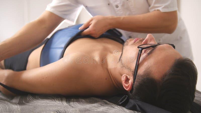 整骨疗法医生执行做法,舒展脊椎,按摩脊柱治疗者,亚洲西藏医学 图库摄影