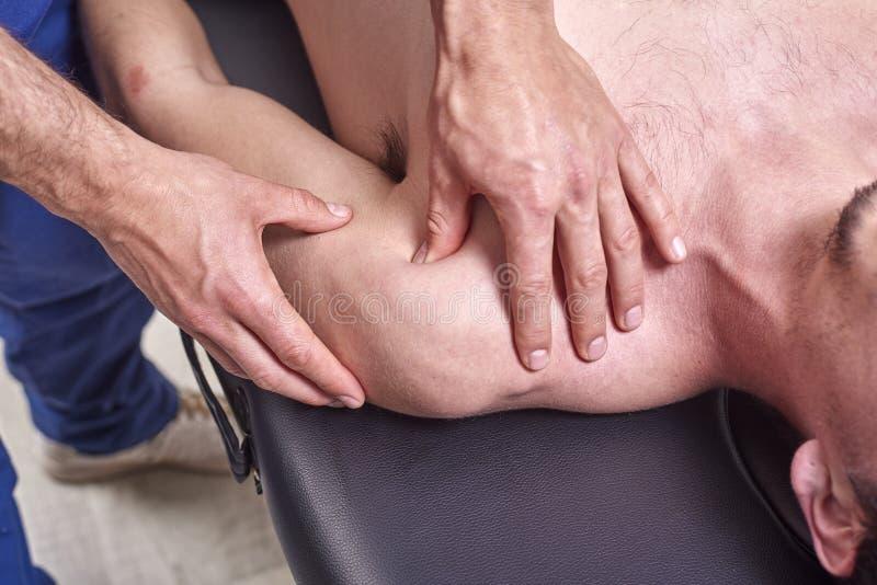 整骨疗法,体育伤害修复概念 遭受背部疼痛和一个理疗师按摩脊柱治疗者的一名男性患者 免版税库存图片