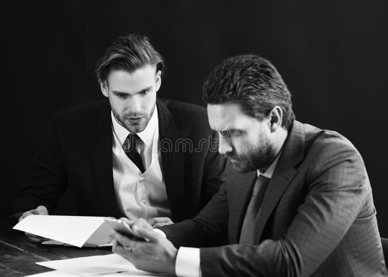 文书工作和财务概念 繁忙的人民读文件并且看智能手机 有胡子和严肃的面孔的人 库存图片