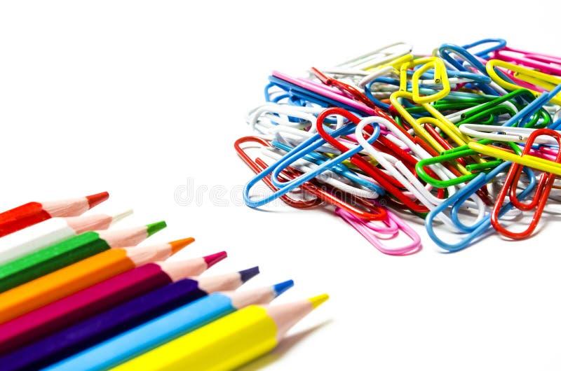 文件和多彩多姿的铅笔的许多多彩多姿的文具夹子在白色背景说谎 免版税库存照片