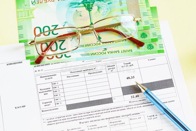 文件用俄语:公共事业的付款的收据 水、玻璃、金钱和一支笔在桌上 库存图片