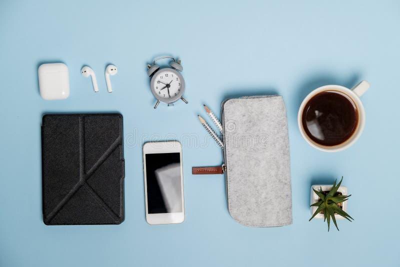 文具、电话、咖啡和耳机在蓝色办公室桌上 T 图库摄影