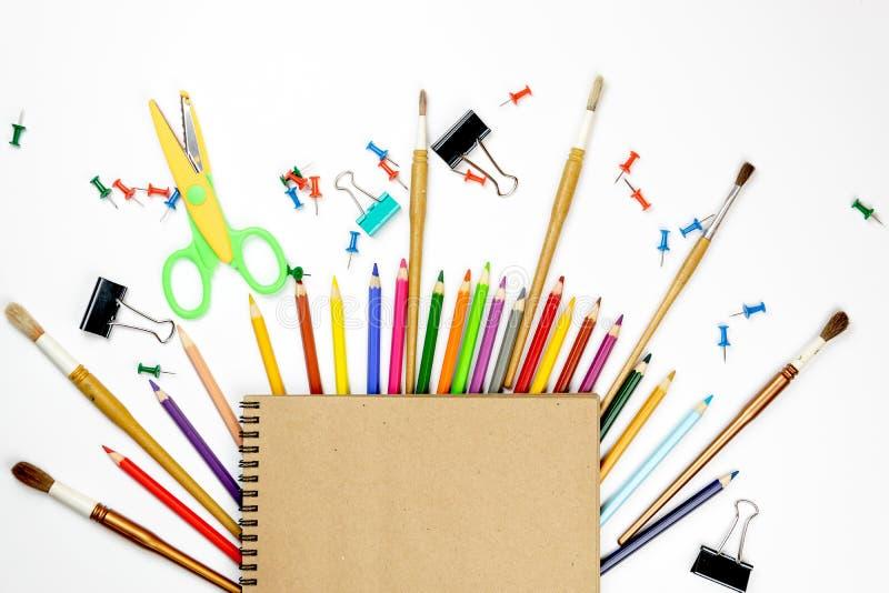 文具五颜六色的书写工具辅助部件笔铅笔,在白色背景隔绝的牛皮纸 r 办公室suppl 免版税库存照片