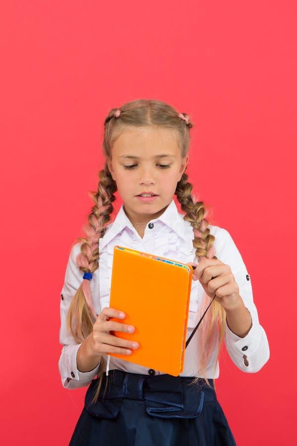 文具钦佩者 女小学生展示笔记薄 学校用品概念 学校文具 买乐趣的逗人喜爱的文具 库存照片