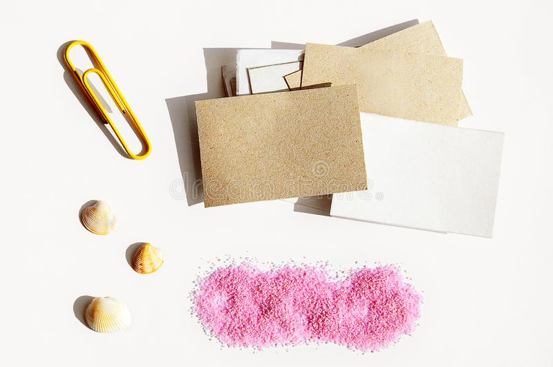 文具项目布局与空间的在轻的背景、纸夹、纸、桃红色沙子和壳的文本的 免版税库存照片