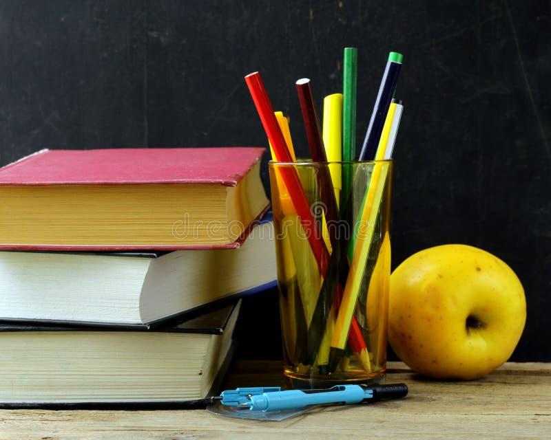 文具(笔、铅笔、统治者,指南针)和在黑校务委员会的一本书 免版税库存照片