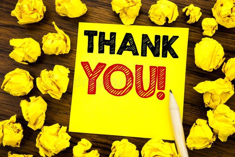 文字文本陈列感谢您 在稠粘的便条纸写的感谢消息的企业概念,与被折叠的ye的木背景 免版税图库摄影