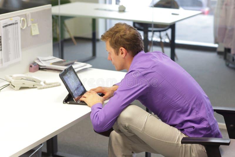 文字颈 — 在桌面上使用平板电脑时处于倾斜位置的人 库存照片