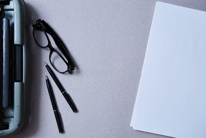 文学、作者和作家、文字和新闻事业概念:葡萄酒打字机和玻璃和一张空白的纸片 库存照片