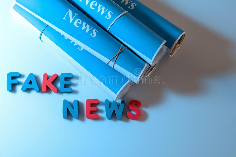 文本伪造品新闻由信件和纸卷制成在颜色背景 库存图片