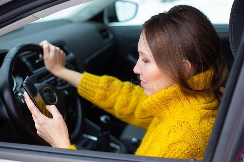 文本和推进妇女 妇女在她的电话发短信,当驾驶时 库存照片