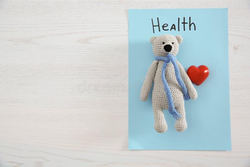 文本的玩具熊、心脏、纸片与词健康的和空间在木背景,顶视图 免版税库存照片